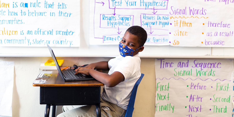 Masked student sitting at desk.