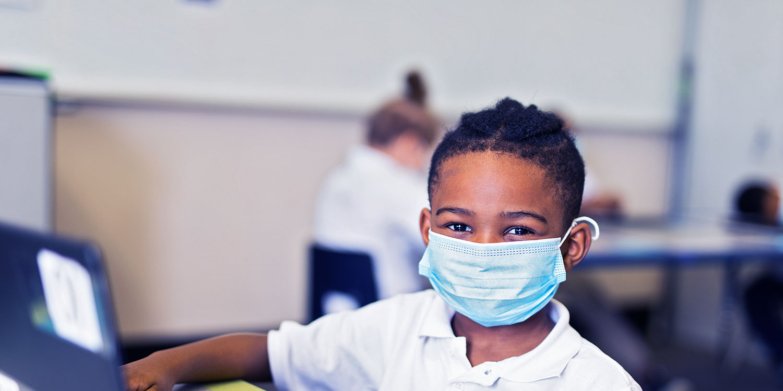 Masked student smiling.